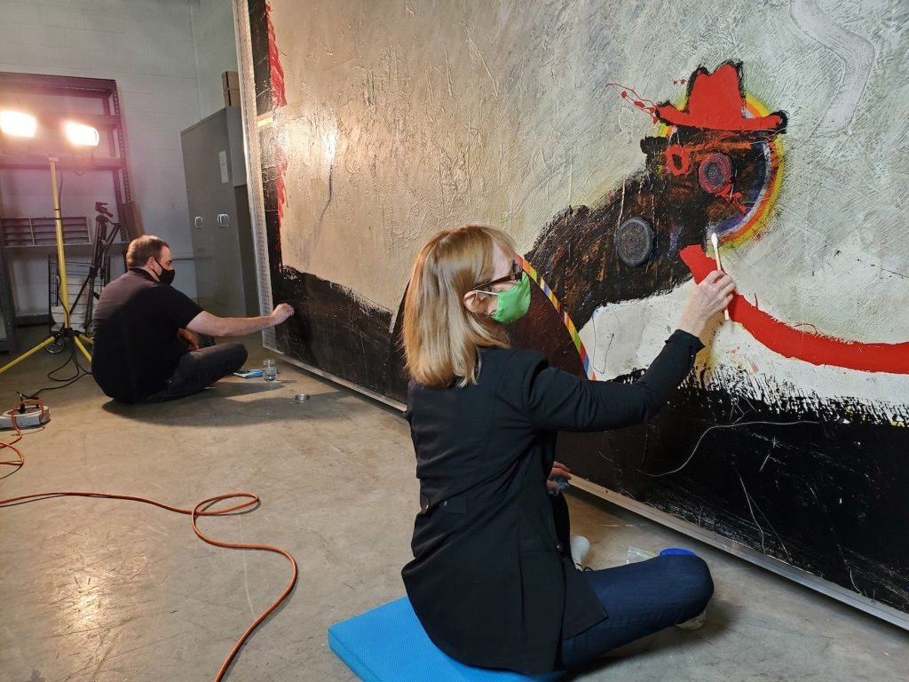 Two art conservators restoring a work of abstract art.