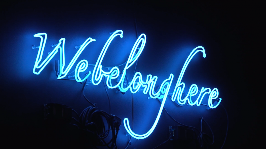 "A blue neon artwork of saying ""We belong here"" in cursive."