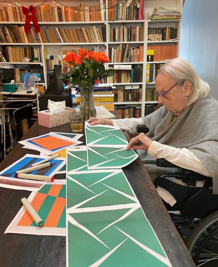 The artist Carmen Herrera sits at a table reviewing plans for an abstract mural. A bookshelf is in the background.