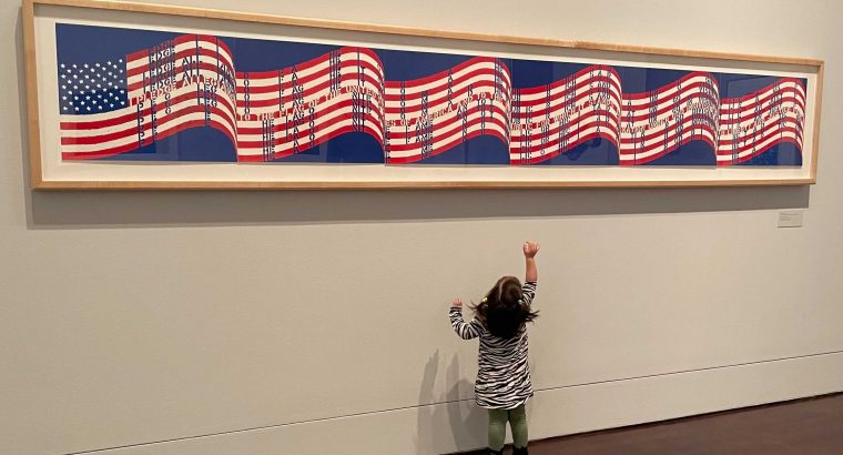 A toddler girl looking up and pointing at a long horizontal print of the USA flag hanging on the wall.