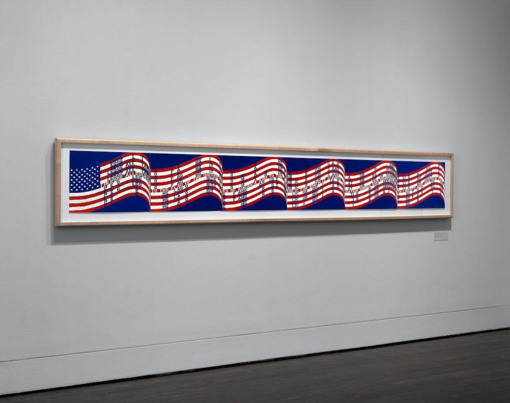 A long horizontal artwork based on the USA flag hanging on a wall.