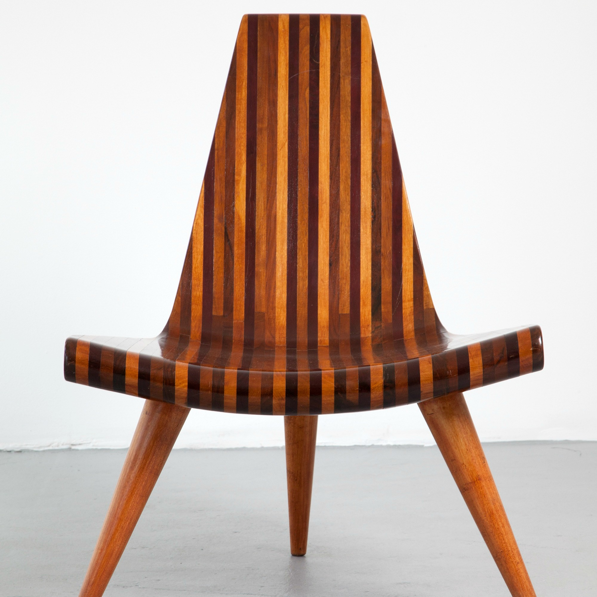 multiple stripes of natually colored wood create the back and base of a three legged chair