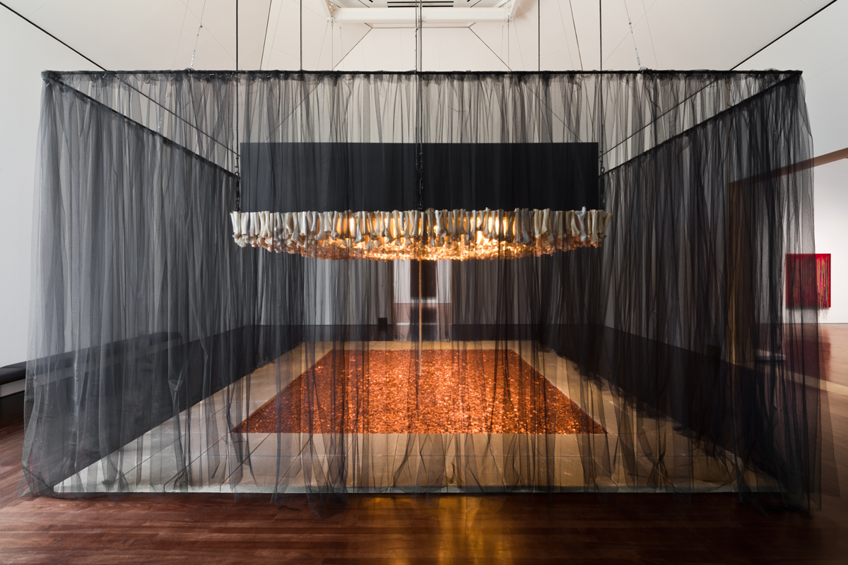 """Photo of Cildo Meireles' Missão/Missões [Mission/Missions] (How to Build Cathedrals) , 1987. The piece is made up of 600,000 coins, 800 communion wafers, 2,000 cattle bones, 80 paving stones, and black cloth. The paving stones are positioned into a rectangle with the interior being full of pennies. In the middle of the pit of pennies is a stack of communion wafers that go towards the top of the piece. The top of the piece is a """"roof"""" of cattle bones positioned vertically. The entire piece is surrounded by a black cloth."""