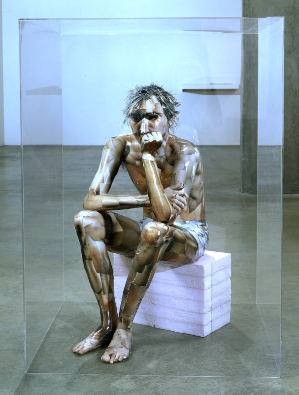 "Image of Oliver Herring's ""Patrick,"" which depicts a sculpture of a seated man whose skin is composed entirely of photographs."