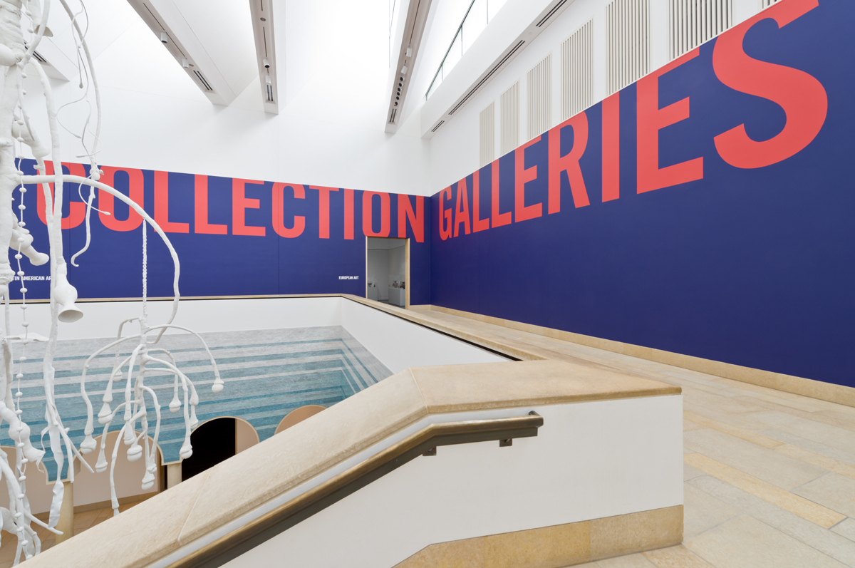 """Top of staircase on the second floor of museum. Wall text reads, """"Collection Galleries."""""""