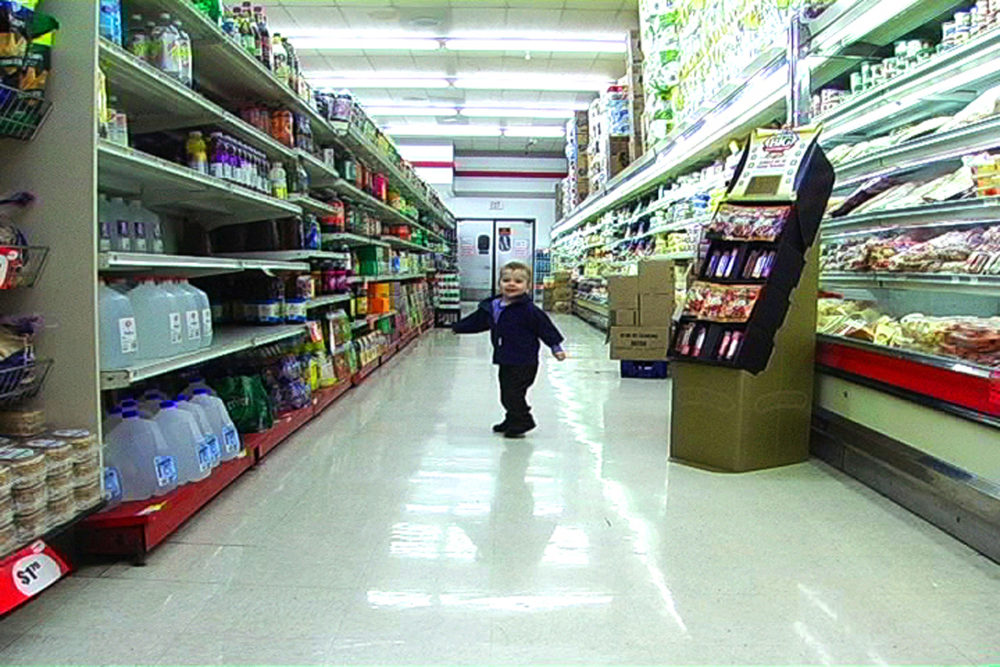 "Still from Lenka Clayton's video series ""The Distance I Can Be From My Son"" set in a supermarket. Clayton's son stands in the middle of a supermarket aisle looking back at the viewer. The left and right are shelves of groceries. There are boxes and a cardboard grocery display to the right of Clayton's son. Behind him are a set of swinging supermarket doors."