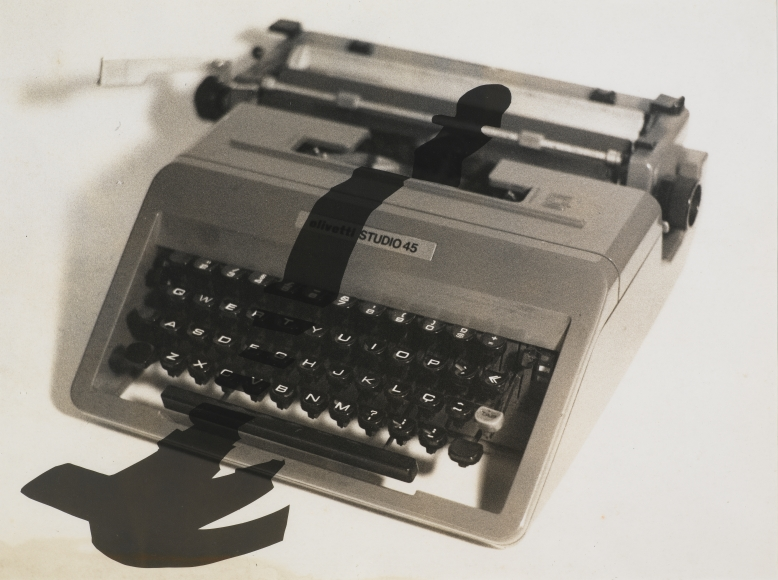 "Photo of ""Enigma 2"" by Regina Silveira the piece features a typewriter with the shadow of a hammer falling over the keys and in front of the typewriter"