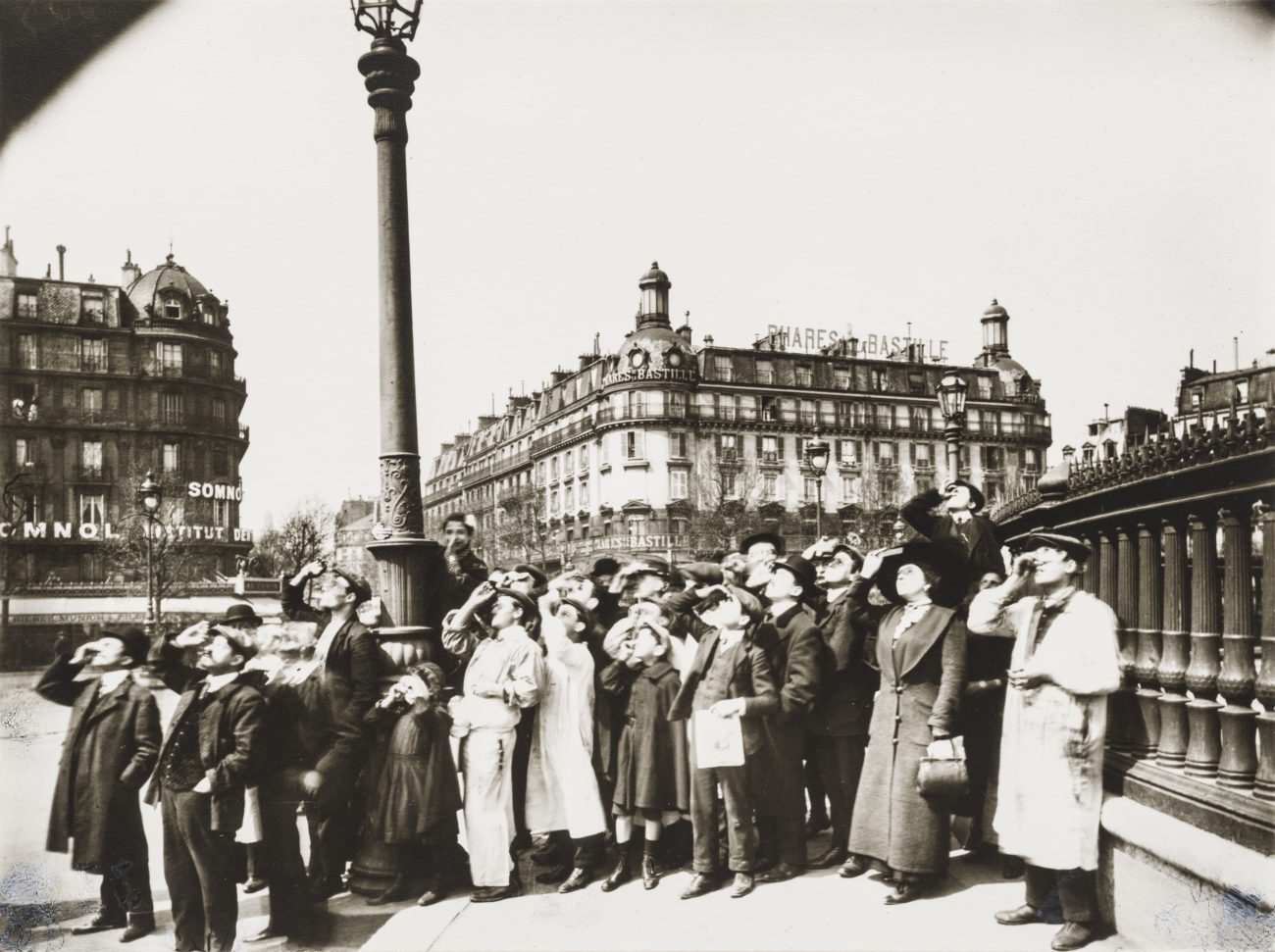 a crowd of people in 19th century dress gather on the streets of paris and look up at the sky through viewfinders during a solar eclipse