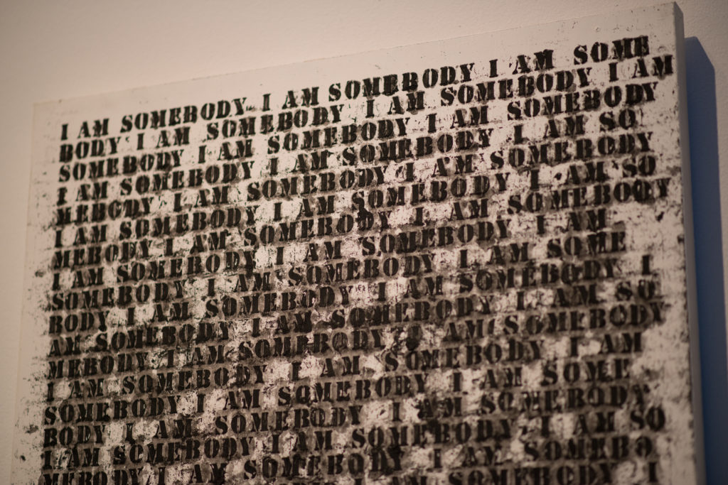 "Oil stick, gesso, and graphite on wood artwork by Glenn Ligon, ""Untitled (I am Somebody)"", it reads ""I am somebody"" repeatedly"