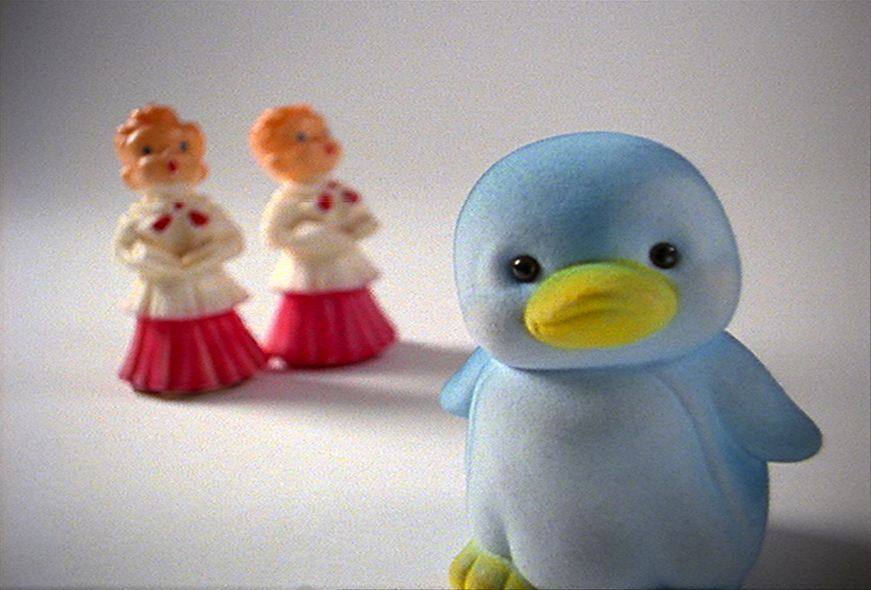 film still featuring a vintage rubber pengiun toy in the foreground and two vintage caroling figures in the background