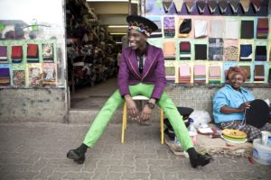 Lethabo Tsatsinyane wearing a purple jacket and green pants sitting on a stool photographed for Dazed magazine, from the Smarteez series