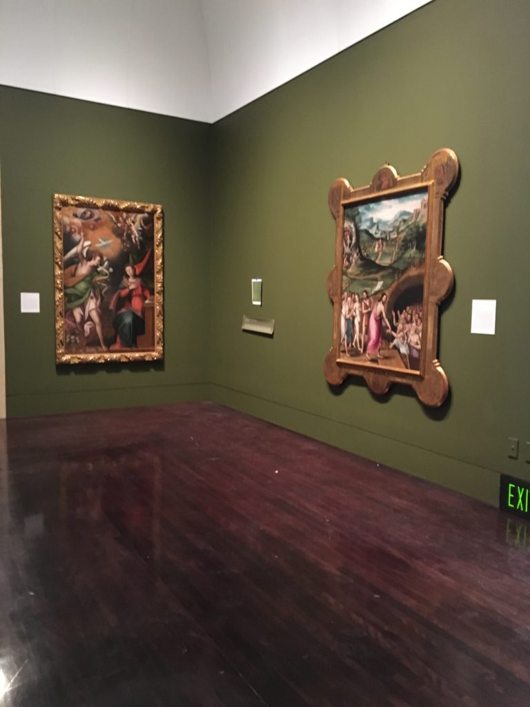 Corner of the Art of the Spanish Americas Gallery at the Blanton Museum of Art, two religious paintings are hung on the walls