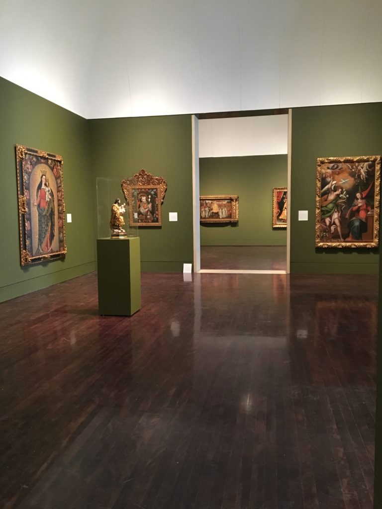 Corner of the Art of the Spanish Americas Gallery at the Blanton Museum of Art, three paintings are hung on the walls and a sculpture is displayed