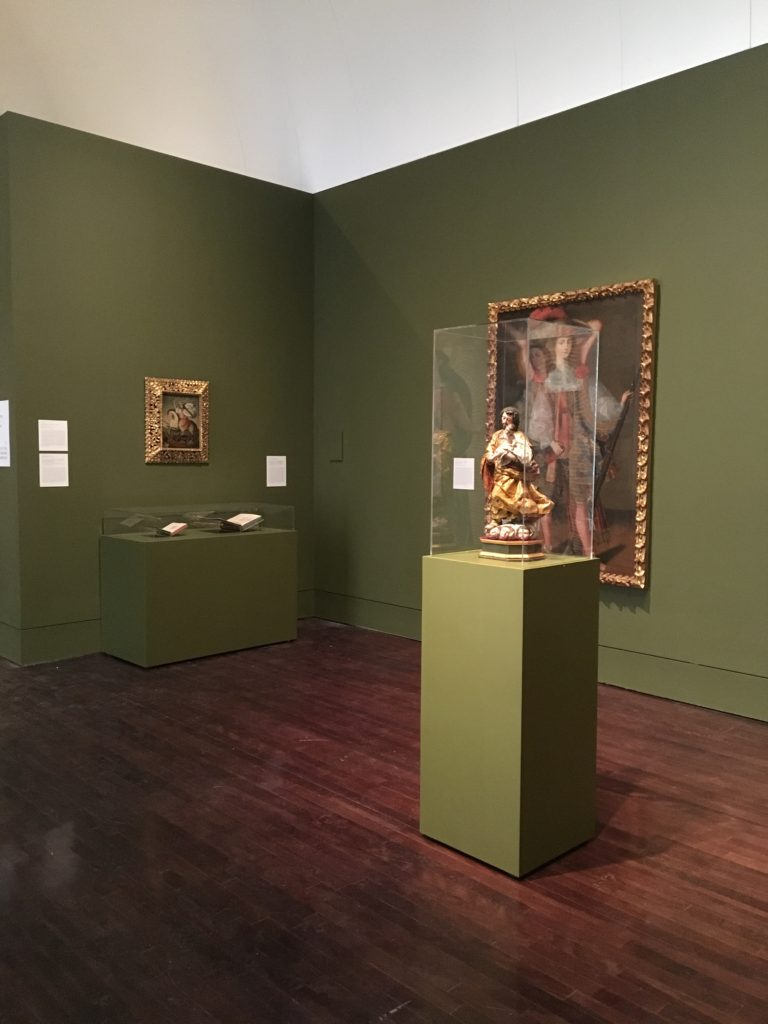 Corner of the Art of the Spanish Americas Gallery at the Blanton Museum of Art, two paintings are displayed on the walls, a sculpture is displayed, and two books are displayed in a case along the wall