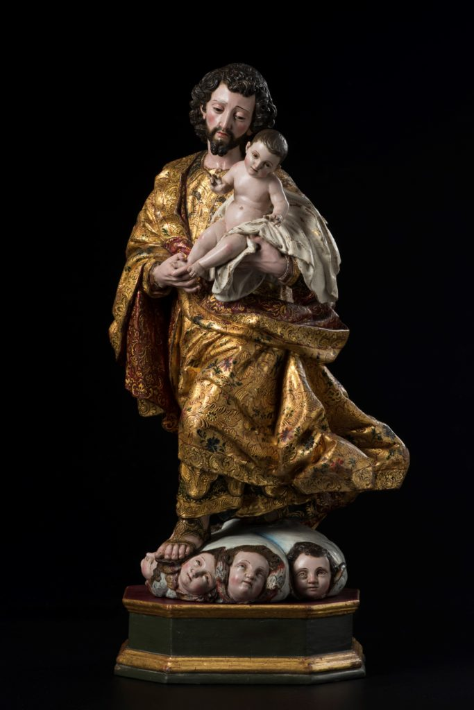 Image of a painted wood statue depicting Joseph in gold robes carrying the infant Jesus while heads of angels look up from the statue's base