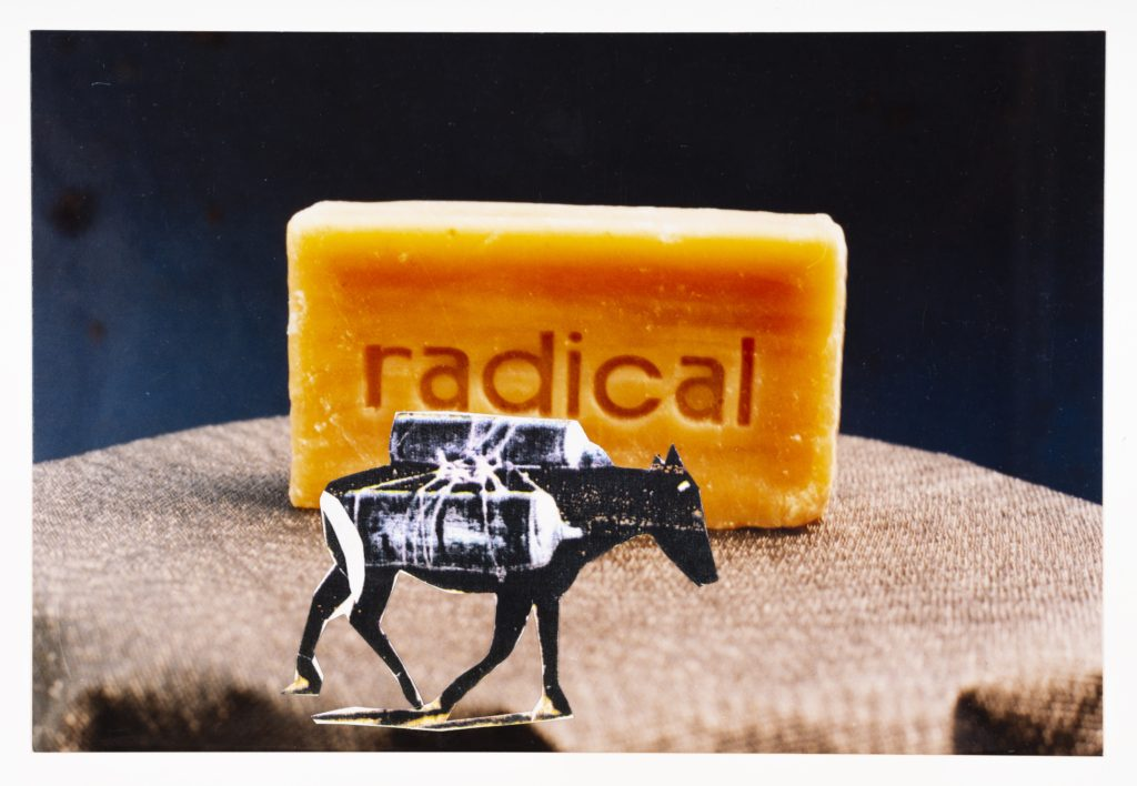 The piece is made out of a collage of photos, paper and stamps. A orange soap bar with radical carved into it sits on a brown cloth covered table. In front oft he soap bar is pasted a donkey with cargo strapped on its back.