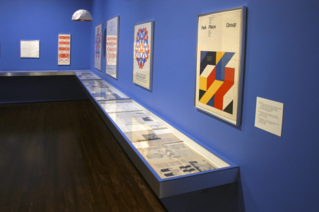 View of a gallery wall in the Reimagining Space exhibition, several artworks are hung on the walls and a case displays artifacts