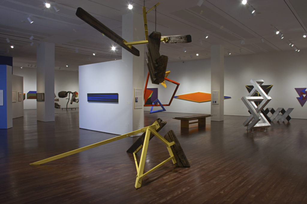 "An abstract sculpture titled, ""The ""A"" Train"" by Mark Di Suvero shown in the Reimagining Space exhibition, other artworks are displayed in the background"