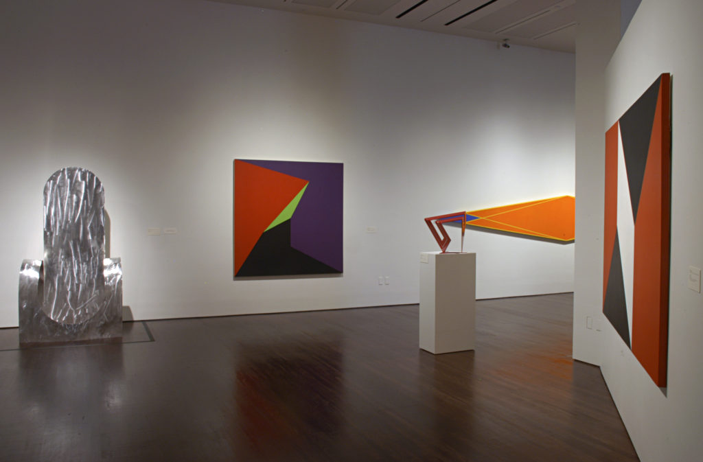 View inside the Reimagining Space exhibition, several abstract artworks are hung on the walls and two sculptures are displayed
