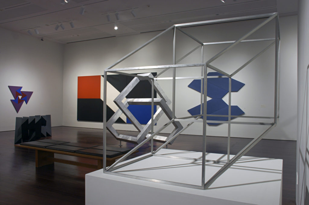 A geometric metal sculpture is displayed on a platform in the Reimagining Space Exhibition, several abstract artworks are displayed in the background