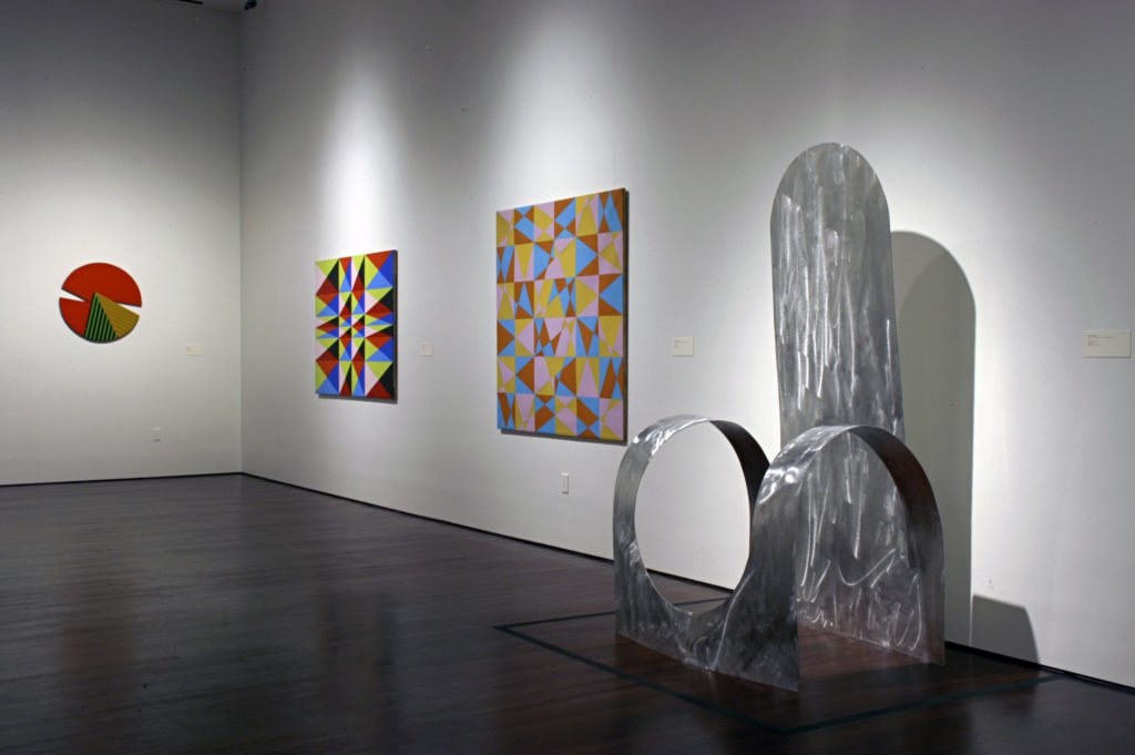 View of a gallery wall in the Reimagining Space exhibition, several abstract artworks are hung on the walls and large abstract sculpture is displayed