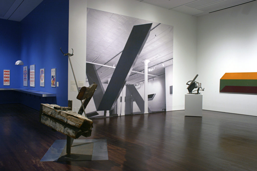 Exhibition View of Reimagining Space: The Park Place Gallery Group in 1960s New York featuring wood and metal sculptures along with colorful prints and paintings.