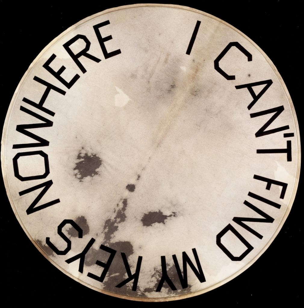 "Artwork by Ed Ruscha, a drumskin head with ""I Can't Find My Keys Nowhere"" painted on it"