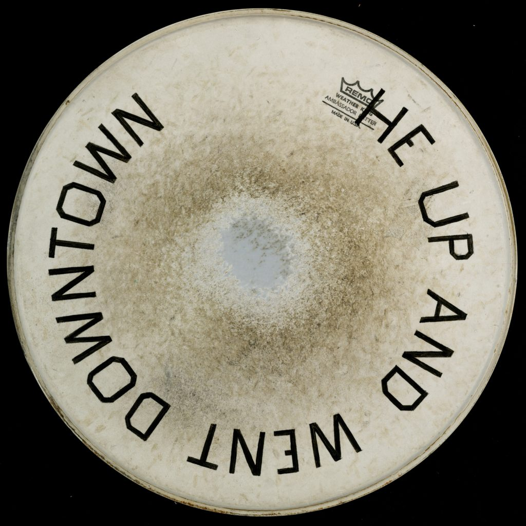 "Artwork by Ed Ruscha, a drumskin head with ""He Up and Went Downtown"" painted on it"