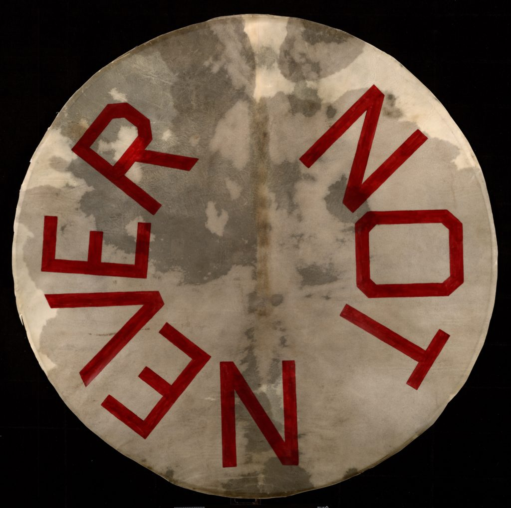 "Artwork by Ed Ruscha, a drumskin head with ""Not Never"" painted on it"