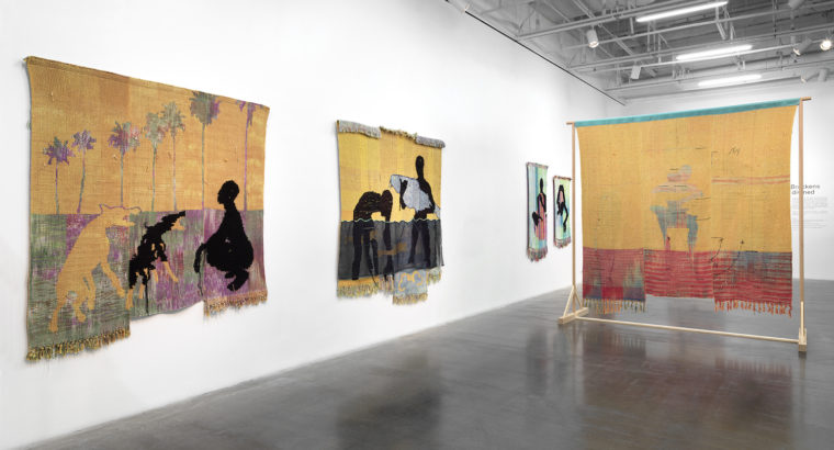 A view of four pieces by Diedrick Brackens, made out of woven cotton and acrylic yarn and silk organza,