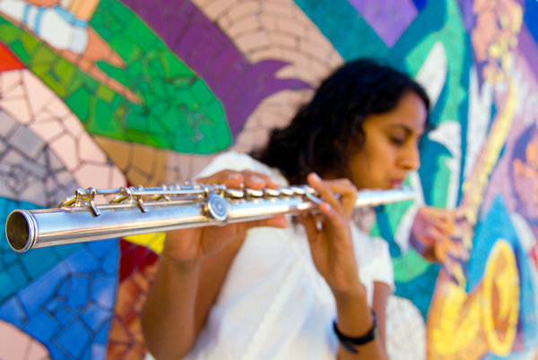 Seetha Shivaswamy playing the flute with a mosaic of a saxophone player in the background.