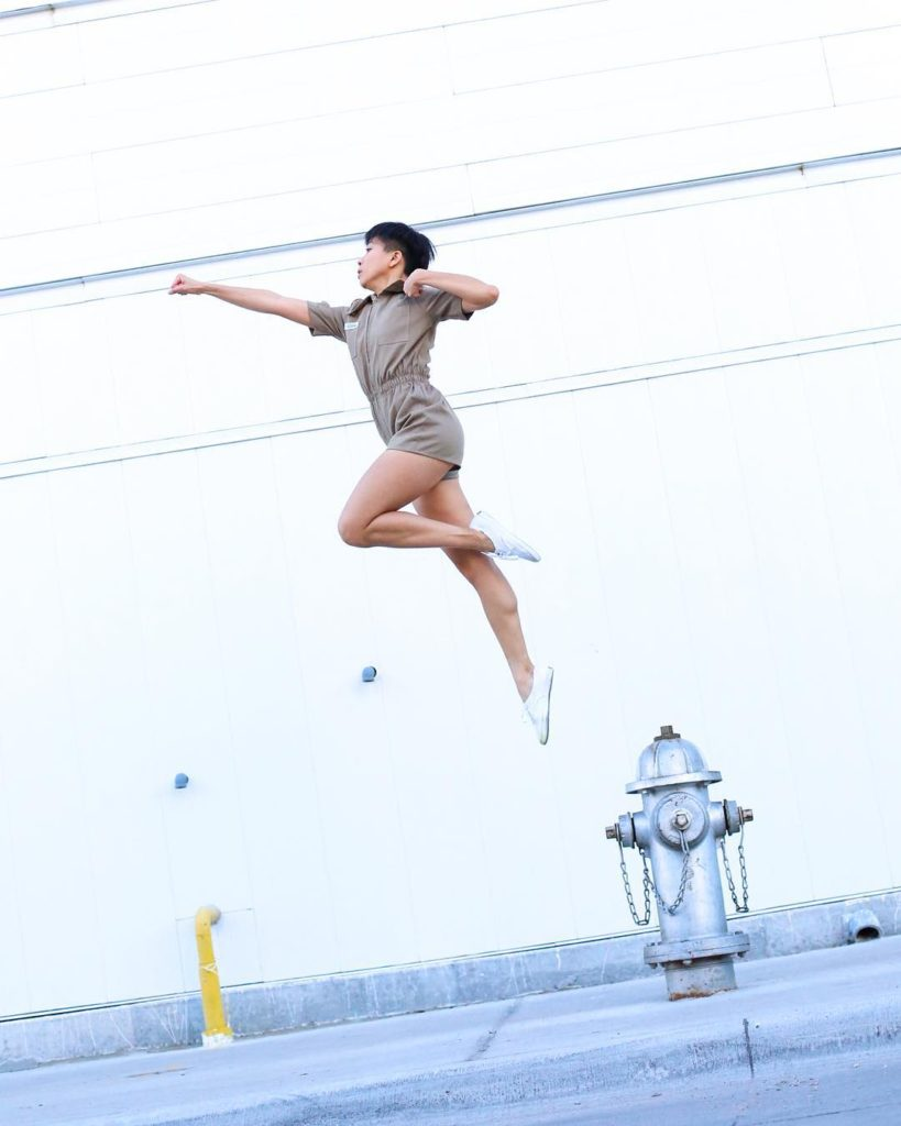 Alexa Capareda, wearing a romper jumpsuit, jumping over a fire hydrant. Arms are in a superhero pose, while one leg is extended downwards and the other is bent in passé.