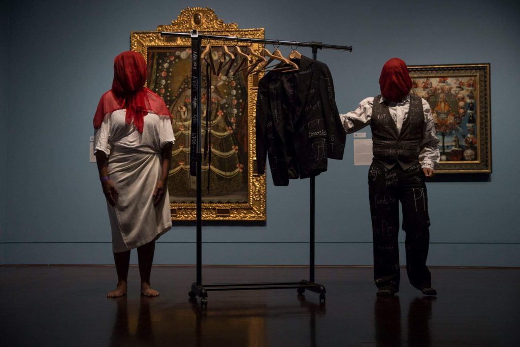 Two figures in an art gallery with red scarves covering their faces. A coat rack with hangers and a coat is between them.