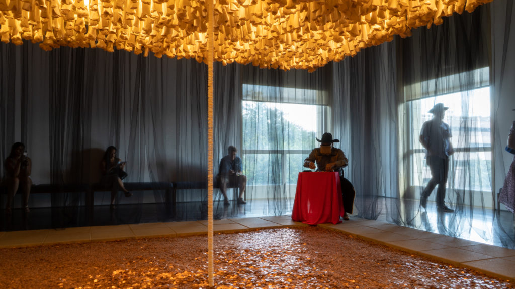 Photo of a performance artist sat in the corner of an exhibition installation of the Blanton Museum of Art