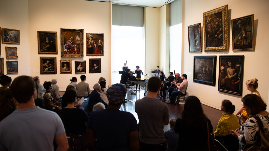 Photo of one of the European galleries of the Blanton Museum of Art during a musical performance of multiple musicians, with a large audience watching.