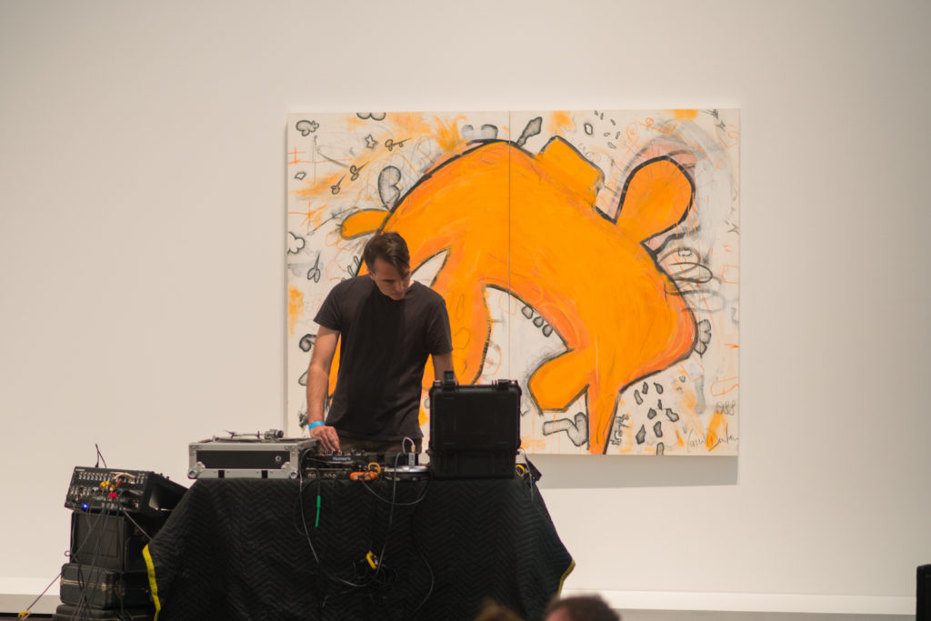 Photo of a male DJ in front of a painting at the Blanton Museum of Art while he is mixing on his deck.