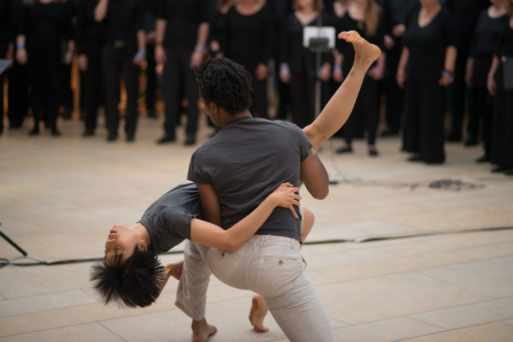 Photo of two dancers performing in front of a choir in the atrium of the Blanton Museum of Art.