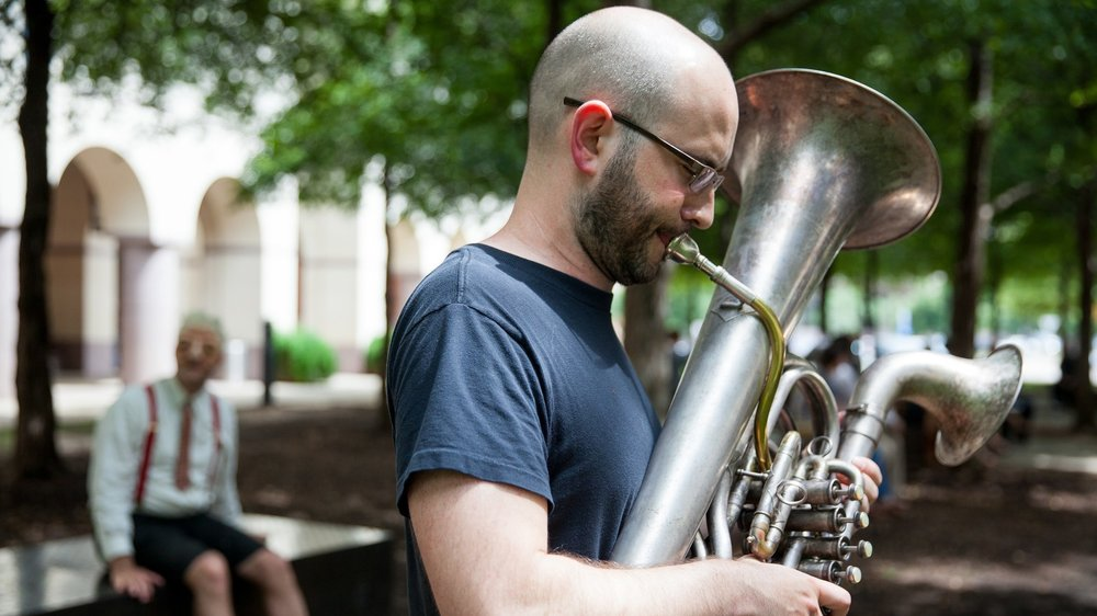 Photo of man playing the tuba in the plaza of the Blanton Museum of Art.