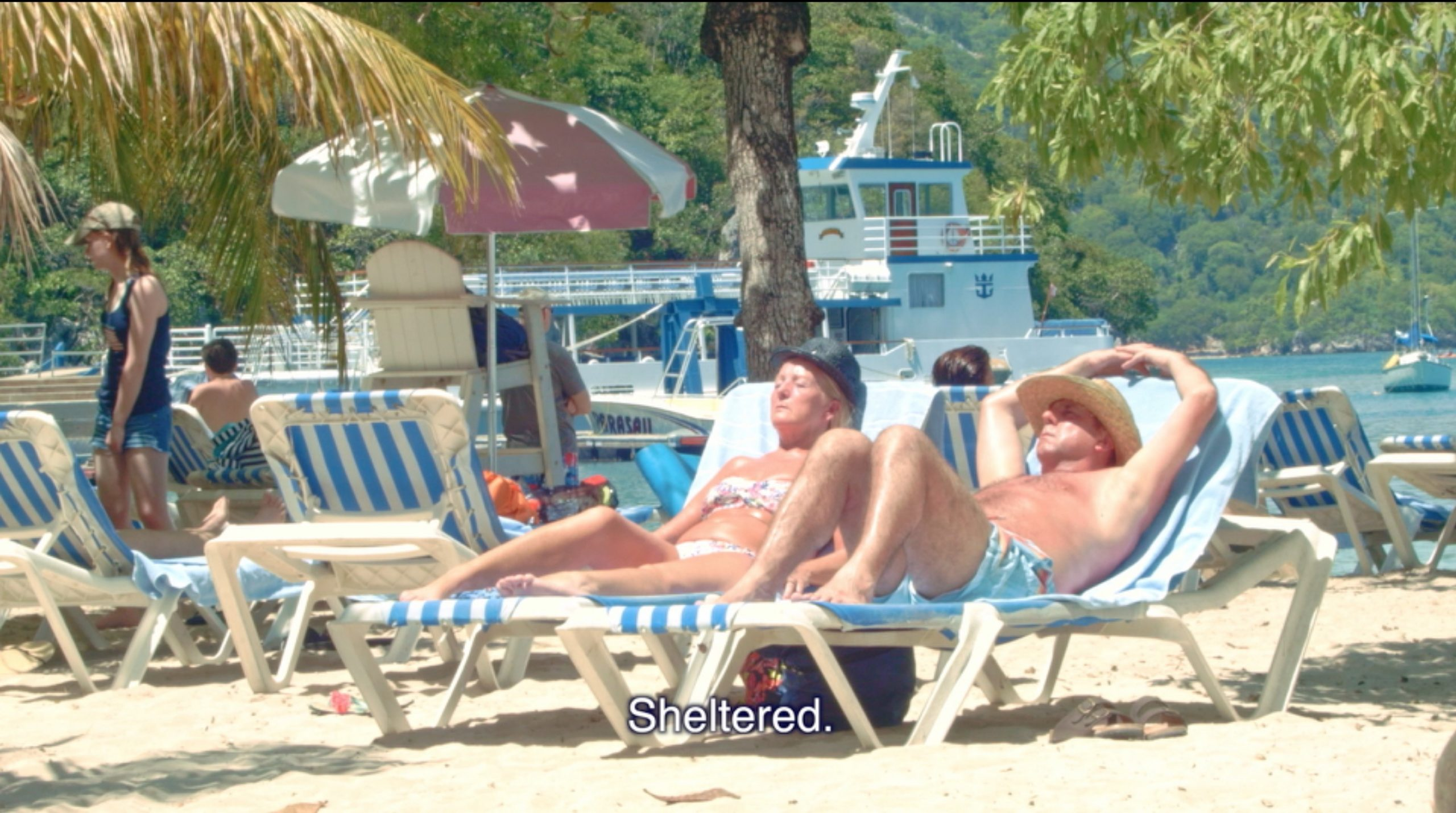 "Joiri Minaya, ""Labadee"" (still) featuring beach goers relaxing in beach chairs with the words ""sheltered"" on the screen, 2017, HD video, 7 min 10 sec, Image courtesy of the artist."
