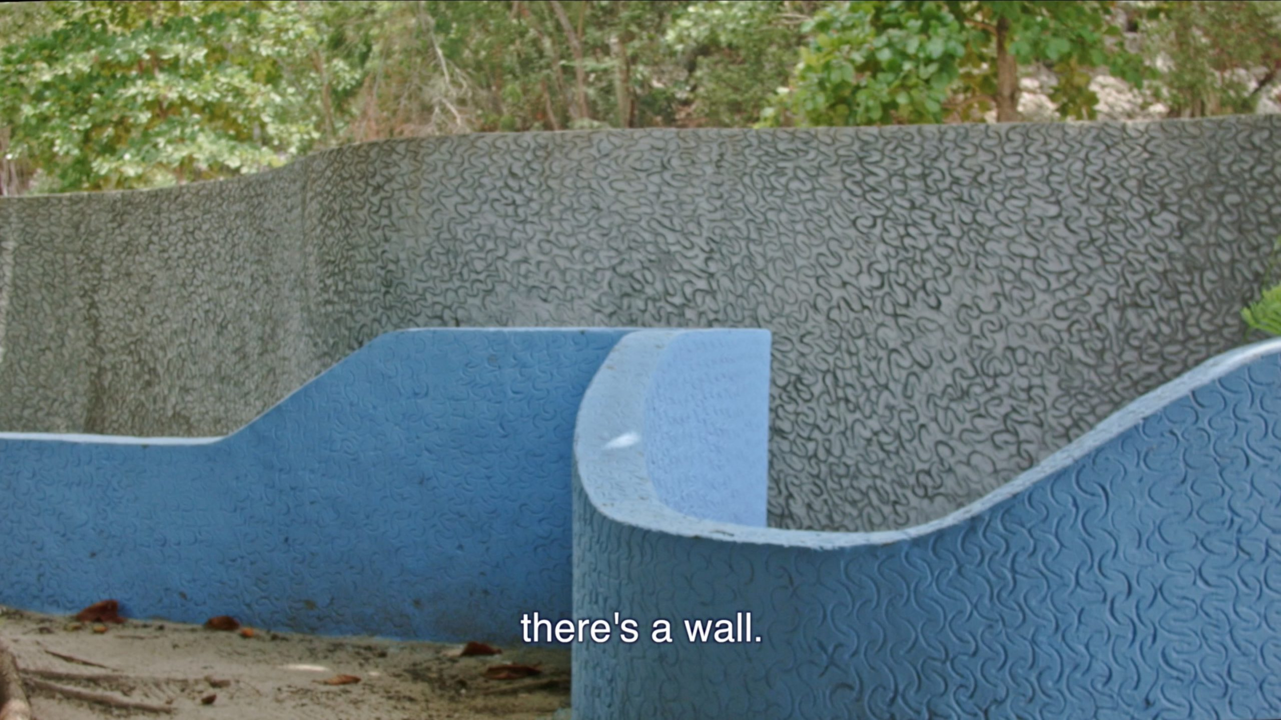 "Joiri Minaya, ""Labadee"" (still) featuring a wall with text that says ""there's a wall,"" 2017, HD video, 7 min 10 sec, Image courtesy of the artist."