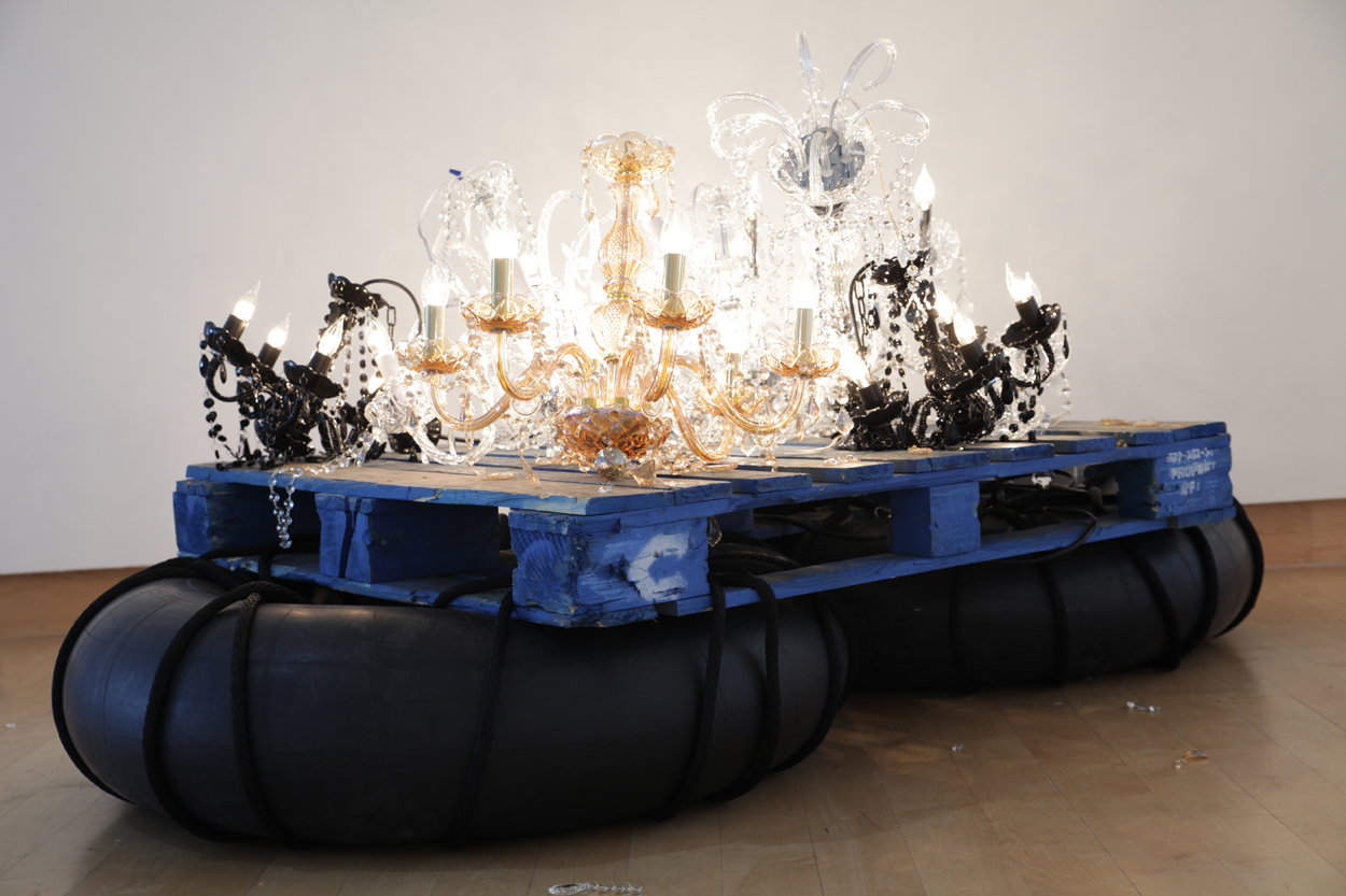 """Fathom""  by Kambui Olujimi, installation with six chandeliers, rubber inner tubes, and wooden pallets"