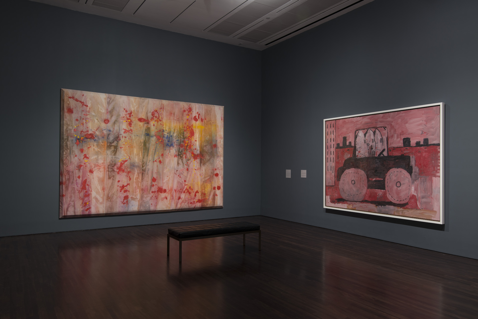 """Installation view of """"Witness: Art and Civil Rights in the Sixties"""" at theBlanton, two artworks are hung on the walls, one is an abstract expressionist work and the other depicts a car driving in a city"""