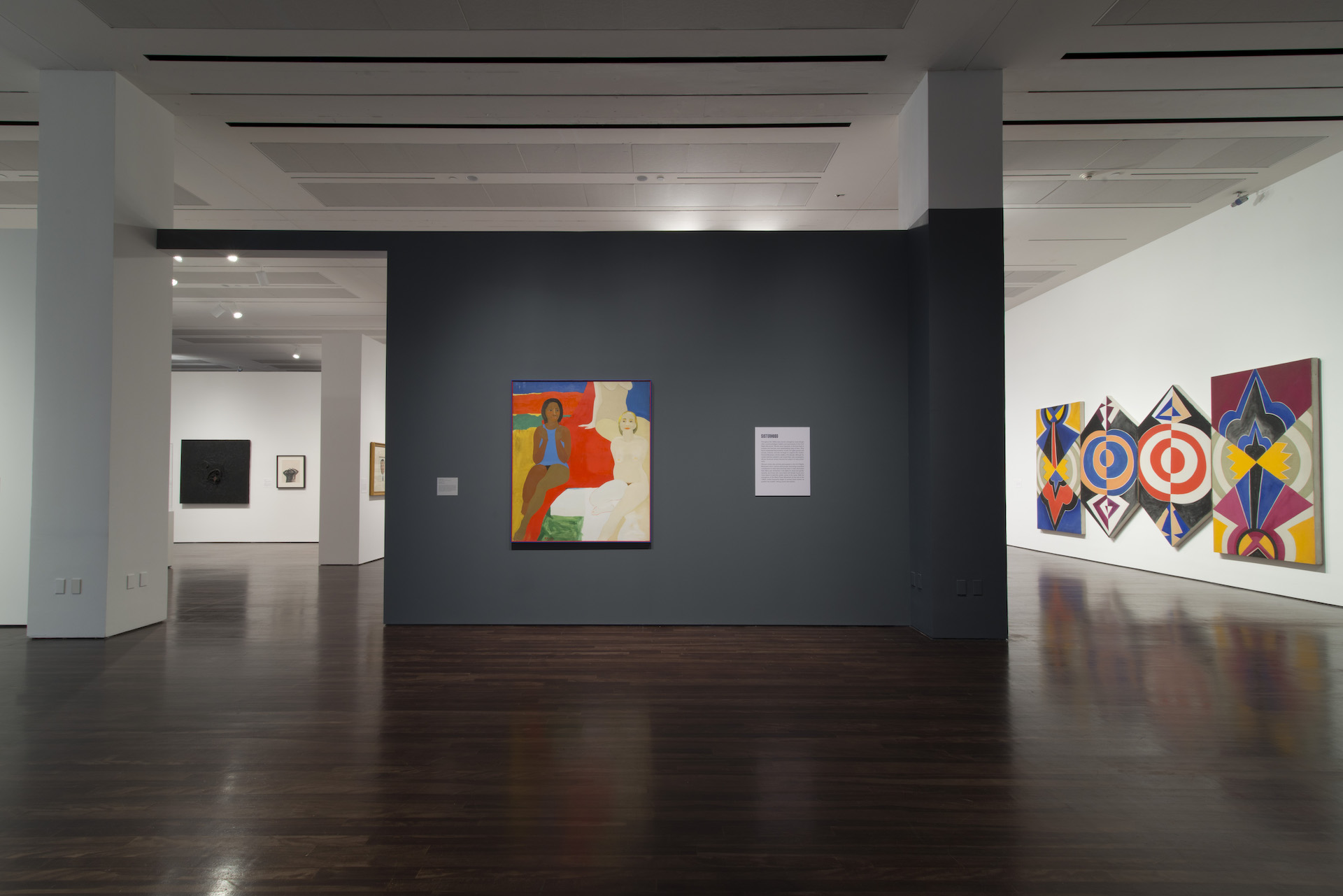 """Installation view of """"Witness: Art and Civil Rights in the Sixties"""" at theBlanton Museum of Art. A grey wall displays a painting featuring nude women. To the right of the wall hangs a painting featuring bold colors and linework."""