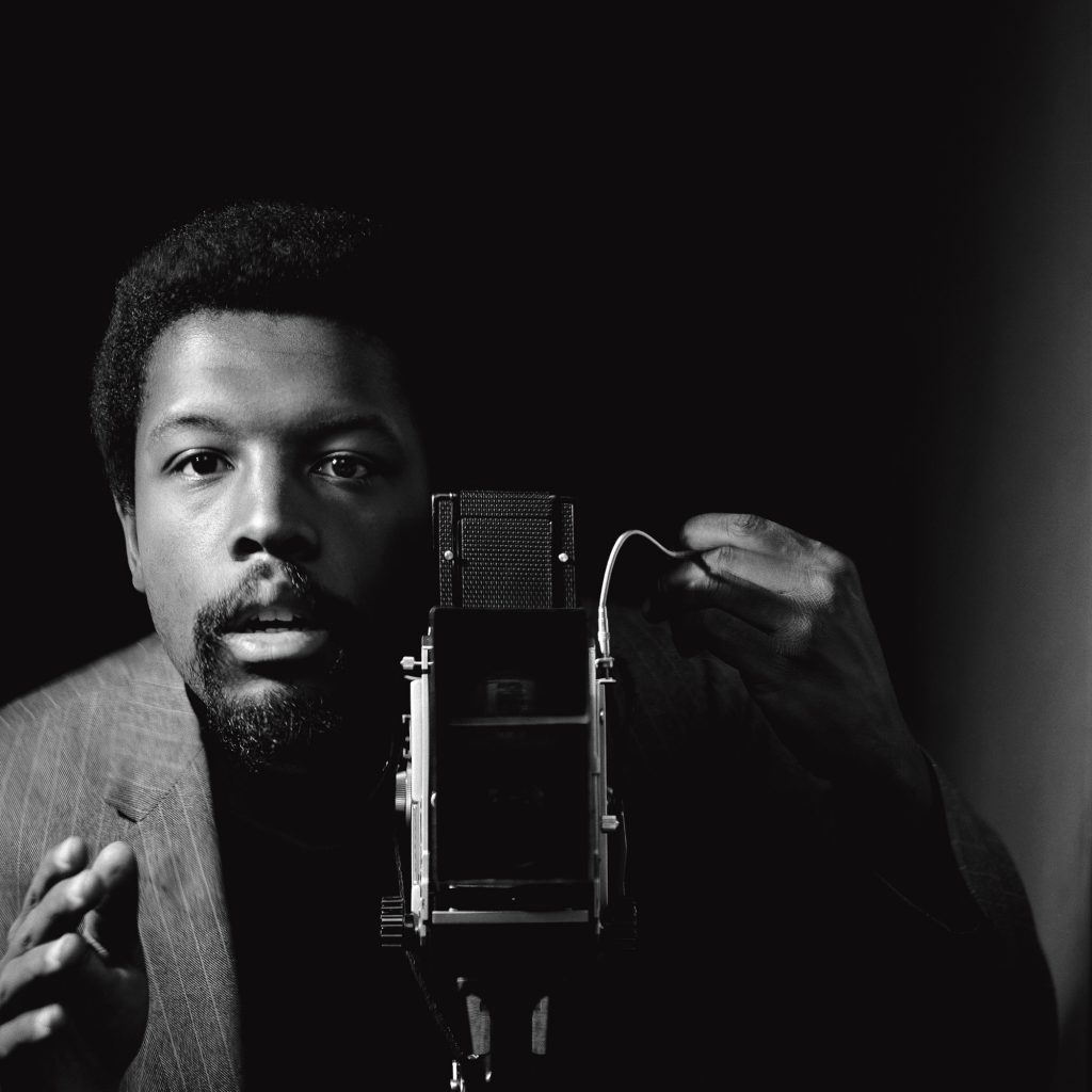 Photo of artist Kwame Brathwaite looking at the viewer with their left hand on the crank of a camera and pointing their right hand toward the viewer
