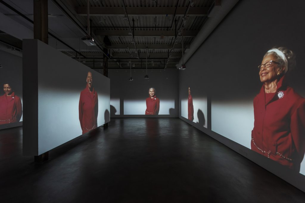 Suzanne Bocanegra, Valley, featuring women wearing red jumpsuits. 2018, installation view at Art Cake, New York. Photo: Alan Tansey, courtesy of the artist.