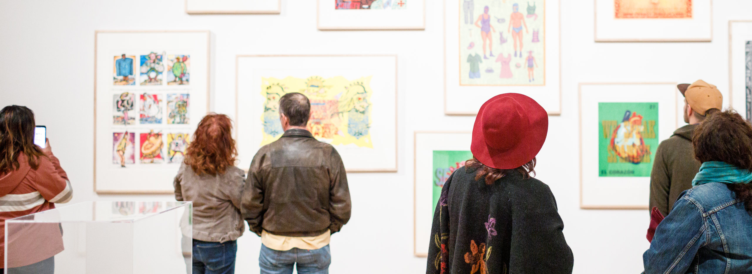 A group of patrons view silkscreen prints displayed on a gallery wall