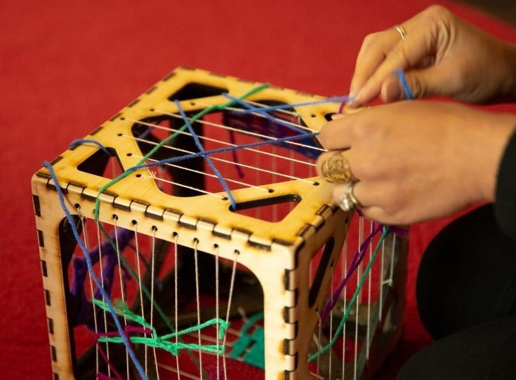 A person's hands weaving across a box for Mindful Weaving activity.