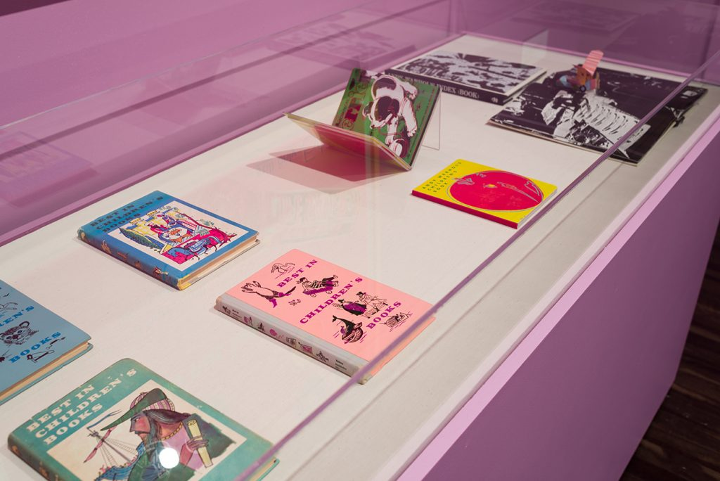 Printed children's books with bright colored illustrations on the covers in a display case