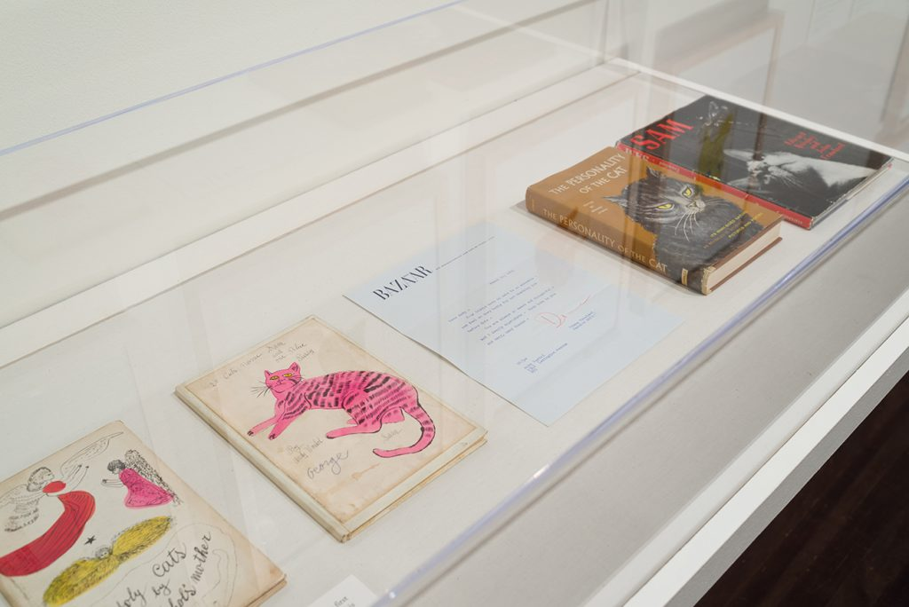 Printed books featuring illustrations of cats and a typed letter in a case