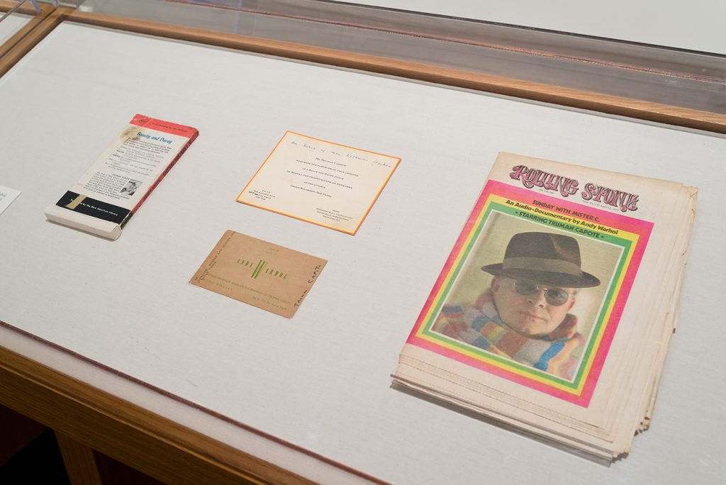 Back cover of a book, a copy of Rolling Stone magazine and two printed cards with some handwritten notes in a display case